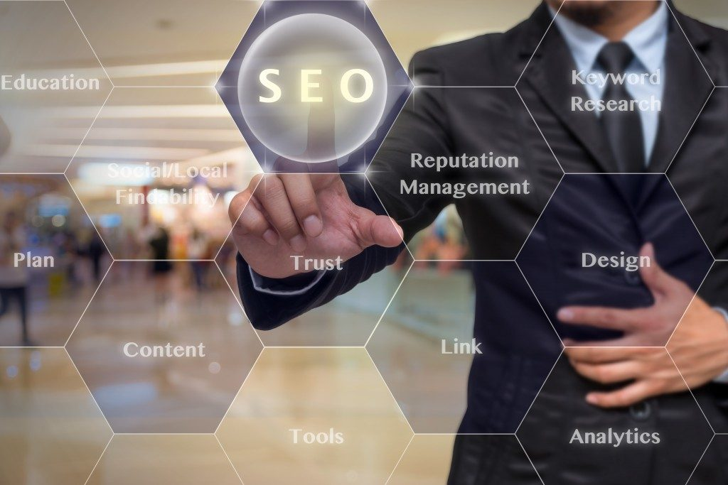 Businessman pressing a futuristic SEO button