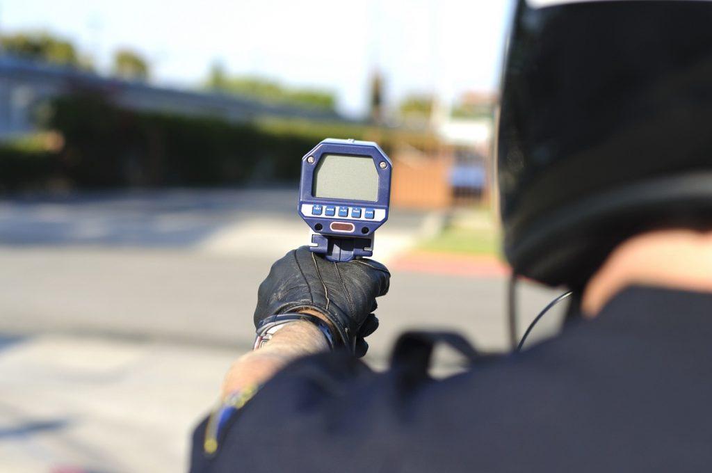 Officer using radar speed gun